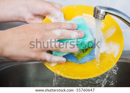 Cleaning dishware kitchen sink sponge washing dish - stock photo