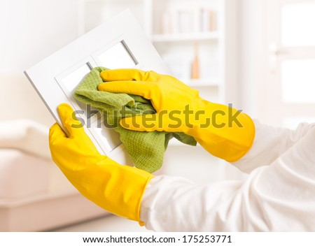 Cleaning frame at home with green cloth - stock photo