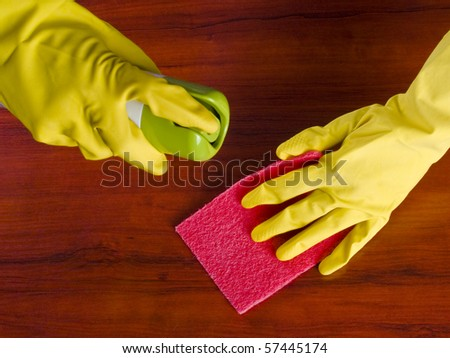 Cleaning furniture table in yellow gloves with red sponge - stock photo