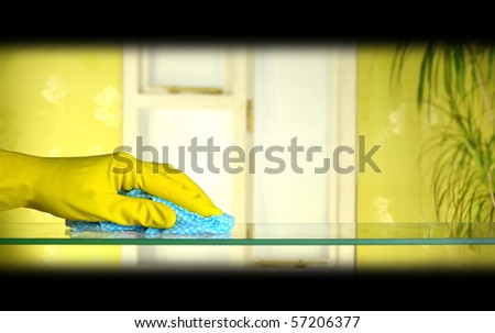 cleaning glass using cloth and yellow rubber gloves - stock photo