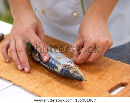 Cleaning herring cook on the kitchen wooden board with selective focus