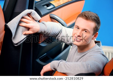 Cleaning his car. Top view of handsome smiling young man cleaning his car dash board with a wiper  - stock photo