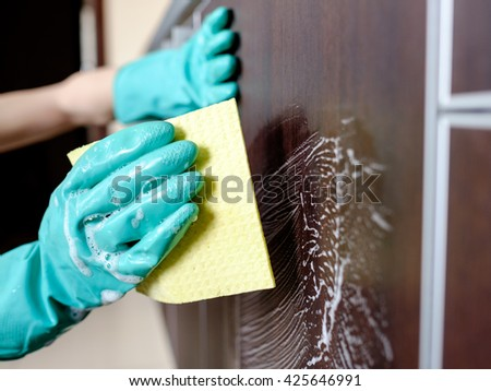 Cleaning house furniture with yellow cloth and detergent - stock photo