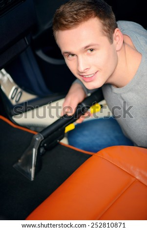 Cleaning in the car. Top view of handsome smiling young man vacuuming his car with a car vacuum cleaner  - stock photo