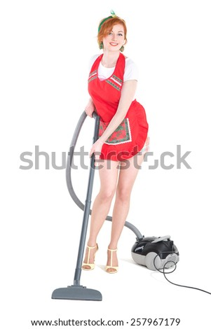 Cleaning is fun. Sexy young housewife cleaning the carpet with vacuum cleaner