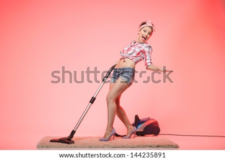 Cleaning is fun. Sexy young housewife cleaning the carpet with vacuum cleaner and dancing - stock photo