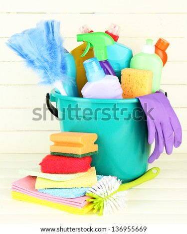 Cleaning items in bucket on  white wooden background - stock photo