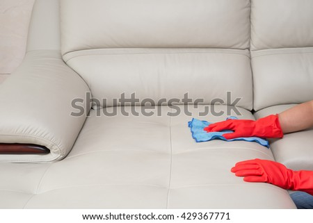 cleaning leather sofa at home - stock photo