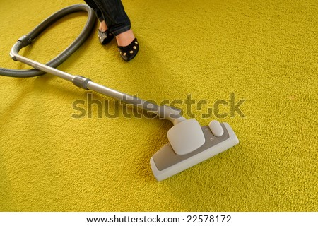 Cleaning of a green carpet with a vacuum cleaner - stock photo