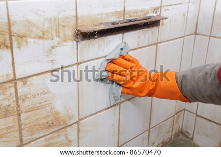Cleaning of dirty old tiles in a bathroom - stock photo