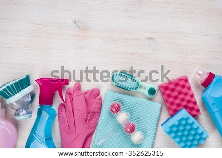 Cleaning products on wooden background with copyspace at the top - stock photo