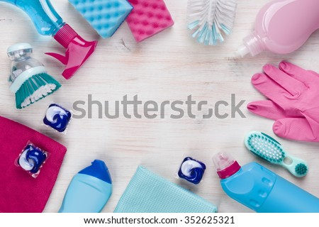 Cleaning products on wooden background with copyspace in the middle - stock photo
