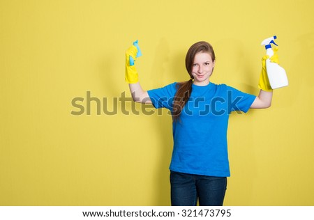 Cleaning service. Maid cleaning woman with cleaning spray bottle. Beautiful cleaning girl isolated on yellow background with copyspace. Mixed race woman. - stock photo