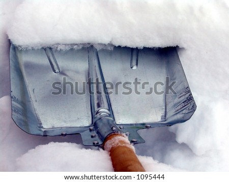 Cleaning snow with a metallic shovel - stock photo