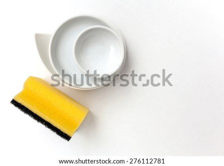 Cleaning sponge and ceramic dish with space on white background - stock photo