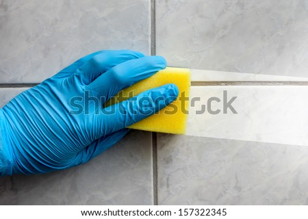 Cleaning sponge held in hand while cleaning bathroom - stock photo