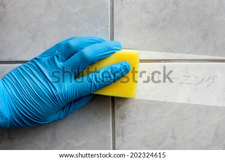 Cleaning sponge held in hand while cleaning bathroom with japanese lettering (cleaning in english translation) - stock photo