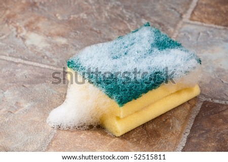 Cleaning sponge on tiled worktop covered with soapy suds - stock photo