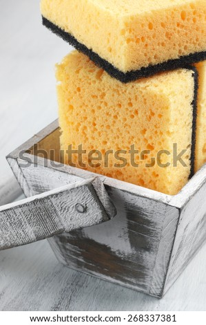 Cleaning sponges in rustic box on wooden background. - stock photo