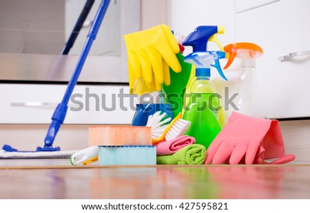 Cleaning supplies and equipment on kitchen floor with oven in background - stock photo
