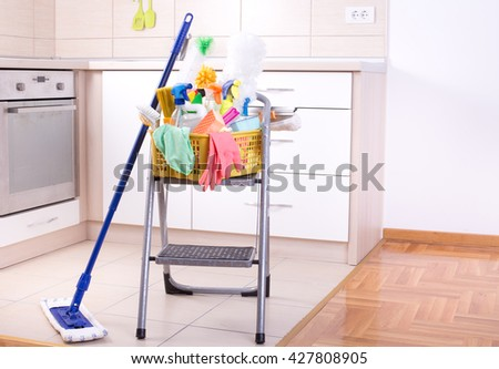 Cleaning supplies in plastic basket on ladder and mop in the kitchen - stock photo
