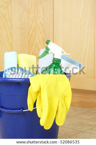 Cleaning supplies on kitchen floor in bucket - stock photo