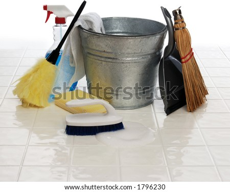 cleaning supplies: spray bottle, broom, duster, wash cloth, scrub brush, bucket, dust pan on white tiles - stock photo