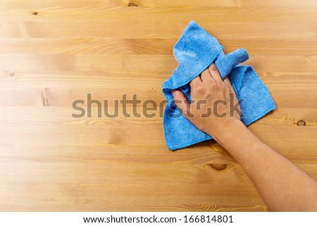 Cleaning table by blue rag - stock photo
