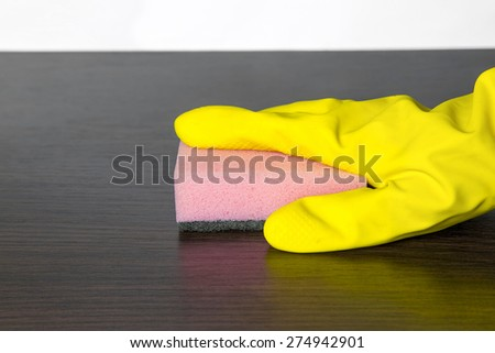 cleaning table in mittens - stock photo