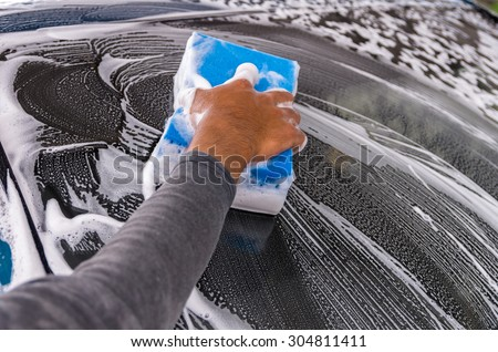 Cleaning the car at car wash shop,car care concept, focus on hand