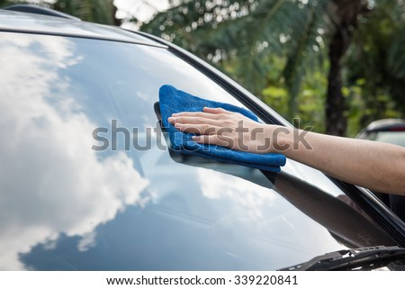 Cleaning the car glass with microfiber cloth - stock photo