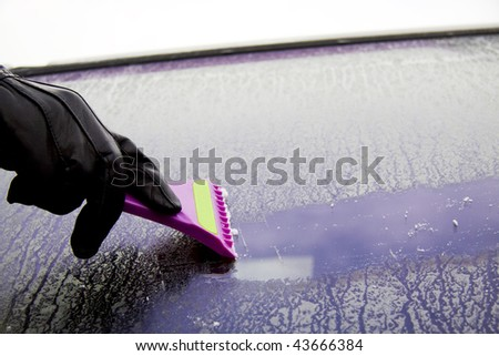 Cleaning the car window with a ice scraper