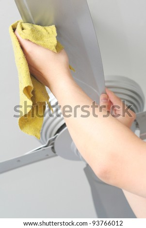 Cleaning the ceiling fan with a cloth - stock photo