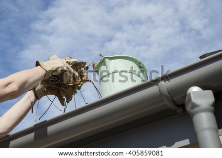Cleaning the home gutters during Autumn - stock photo