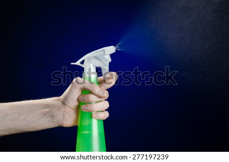 Cleaning the house and cleaner theme: man's hand holding a green spray bottle for cleaning on a dark blue background in studio - stock photo