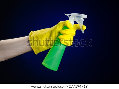 Cleaning the house and cleaner theme: man's hand in a yellow glove holding a green spray bottle for cleaning on a dark blue background in studio - stock photo