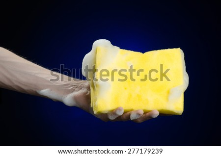 Cleaning the house and sanitation topic: Hand holding a yellow sponge wet with foam on a dark blue background in studio - stock photo