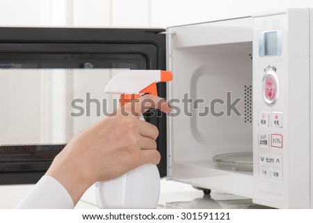 cleaning the microwave oven - stock photo