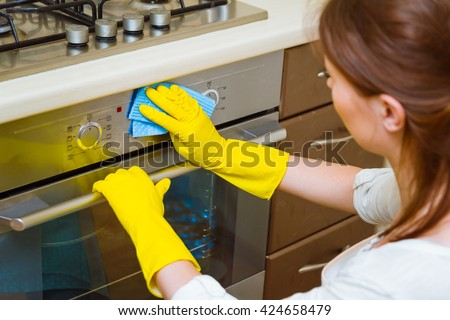 Cleaning the oven concept. Woman in gloves and an apron in the kitchen washing the oven door - stock photo