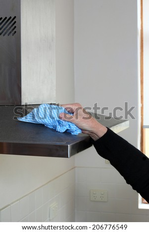 Cleaning the range hood in the kitchen. - stock photo