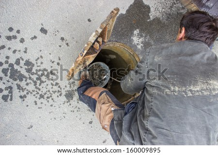 cleaning the sewers, blocked drain cleaning. two man crew are cleaning out the distribution lines below the streets. one man of the crew is in a hole, the other is up.  - stock photo