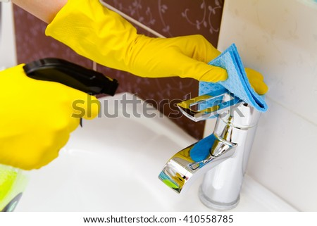Cleaning the tap in the bathroom. Cleaning the bathroom concept - stock photo