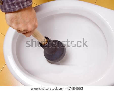 Cleaning toilet bowl with lavatorial bell. Man's hand cleans clogged toilet. Clean blocked drain the toilet bowl. Maintain cleanliness of drains in the bathroom. Service of plumbers. - stock photo