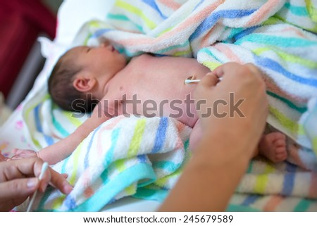 Cleaning umbilical in a newborn baby - stock photo