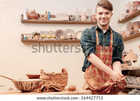Cleaning up after work. Young cheerful potter cleaning his hands with his apron standing by the pottery wheel in clay studio - stock photo