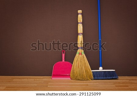 Cleaning up the apartment: brooms and a dustpan - stock photo