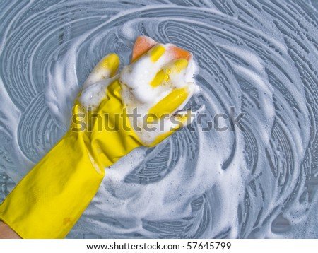 Cleaning window hand in yellow glove with sponge foam