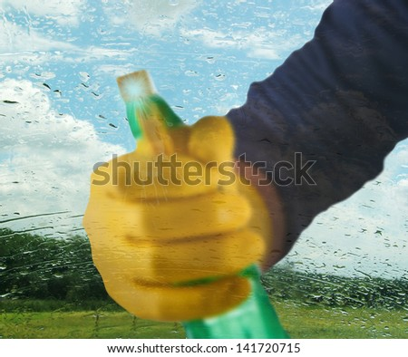 Cleaning window pane with spray detergent - stock photo