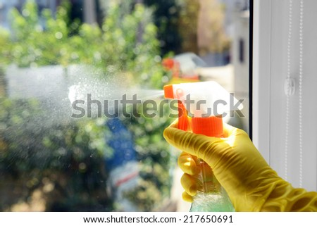 Cleaning window with special cleaner - stock photo