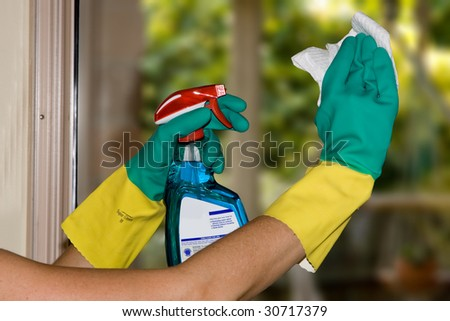Cleaning windows with kitchen towels and detergent spray - stock photo
